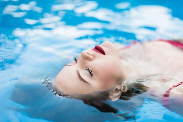 Jonge lachende vrouw in bikini ontspannen koelen, zwemmen op rug in helder water in zwembad. heet mooi meisje in badmode ligt in water op de zon op zomervakantie.