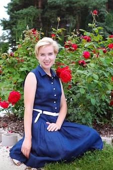 Jonge lachende vrouw in een blauwe jurk in een stadspark tussen groen en rozen