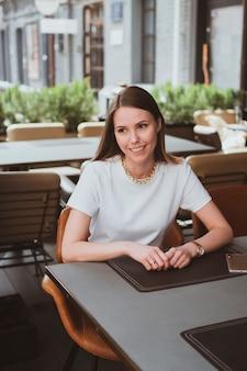Jonge lachende vrouw in een straatcafé