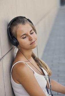 Jonge lachende vrouw in een wit t-shirt met muziek luisteren en zittend op de stoep
