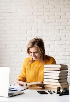 Jonge lachende vrouw in gele trui studeren met behulp van laptop en lezen van een boek