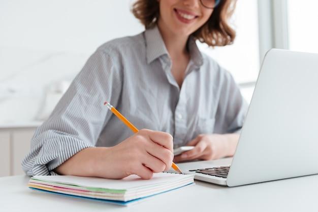 Jonge lachende vrouw in gestreept shirt het maken van aantekeningen zittend aan tafel in lichte appartement