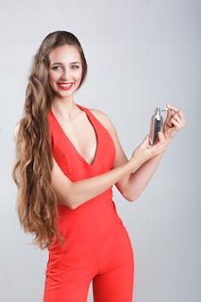 Jonge lachende vrouw in rode jurk met parfum