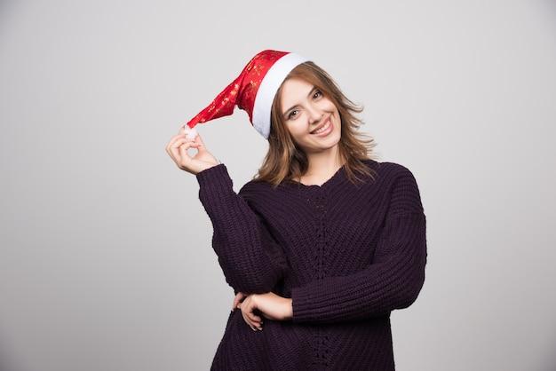 Jonge lachende vrouw in santa's hoed staan en poseren.