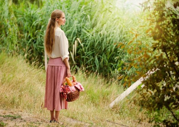 Jonge lachende vrouw in vintage retro stijl kleding houdt een picknickmand in haar hand tegen de achtergrond van riet op het meer