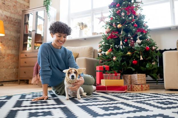 Jonge lachende vrouw in vrijetijdskleding kijken naar grappige hond in gebreide hoofddeksels terwijl ze allebei op de vloer van de woonkamer bij de kerstboom zitten