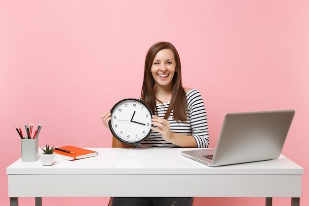 Jonge lachende vrouw in vrijetijdskleding met een ronde wekker zit aan het werk aan een wit bureau met een moderne pc-laptop