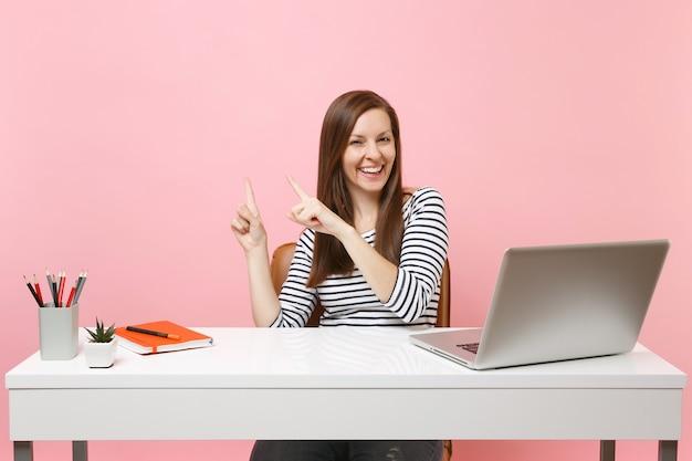 Jonge lachende vrouw in vrijetijdskleding wijst wijsvinger opzij, zit, werkt aan een wit bureau met een moderne pc-laptop