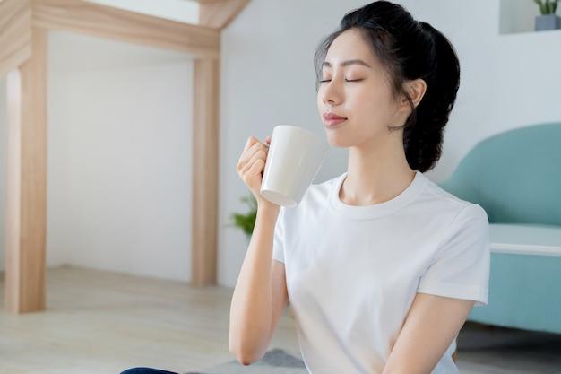 Jonge lachende vrouw in wit t-shirt geniet van een kopje koffie