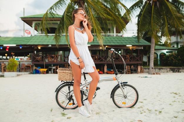 Jonge lachende vrouw in witte jurk rijden op tropisch strand op fiets zonnebril reizen op zomervakantie in thailand