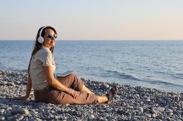 Jonge lachende vrouw in witte koptelefoon en zonnebril luisteren naar muziek op het kiezelstrand