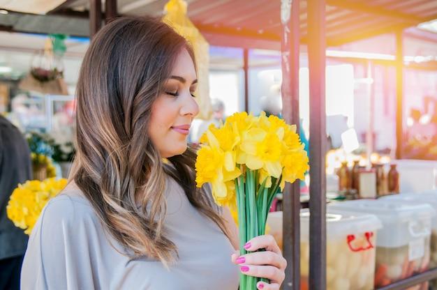 Jonge lachende vrouw kiezen van verse bloemen. close-up profiel portret van een mooie en jonge vrouw genieten van en ruiken een boeket bloemen terwijl ze staan in een verse bloemenmarkt kraam tijdens een zonnige dag in openlucht.