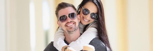 Jonge lachende vrouw knuffelt man in zonnebril op straat