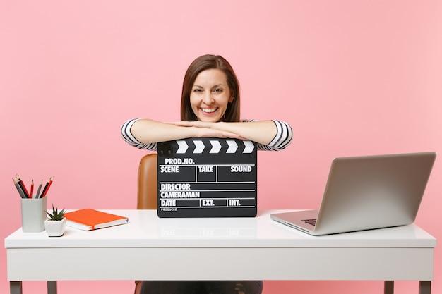 Jonge lachende vrouw leunend op klassieke zwarte film filmklapper maken en werken aan project zittend op kantoor met laptop geïsoleerd op roze achtergrond. prestatie zakelijke carrière. ruimte kopiëren.