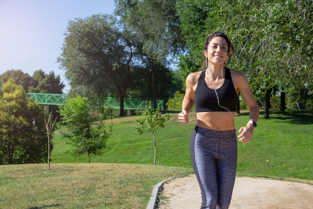 Jonge lachende vrouw loopt door een park op een zonnige dag terwijl ze naar muziek luistert met een koptelefoon