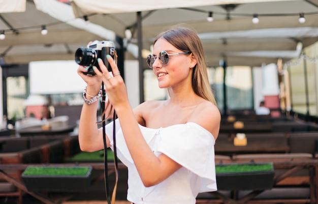 Jonge lachende vrouw maakt foto's met een retro camera op terras