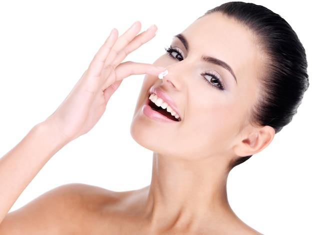 Jonge lachende vrouw met cosmetische crème op een vrij fris gezicht - geïsoleerd op wit