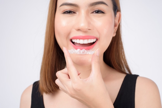 Jonge lachende vrouw met invisalign beugels in studio, tandheelkundige gezondheidszorg en orthodontisch concept