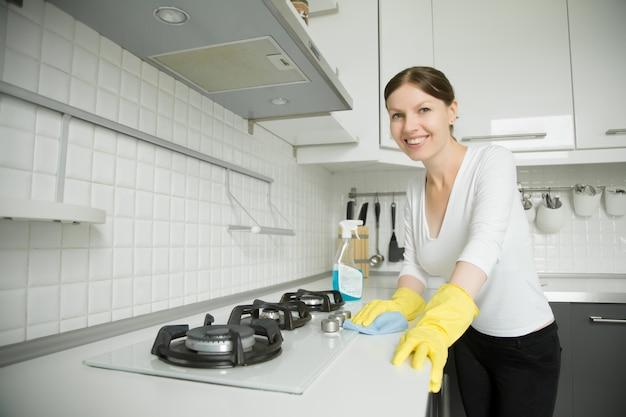 Jonge lachende vrouw met rubberen handschoenen die de kachel schoonmaken