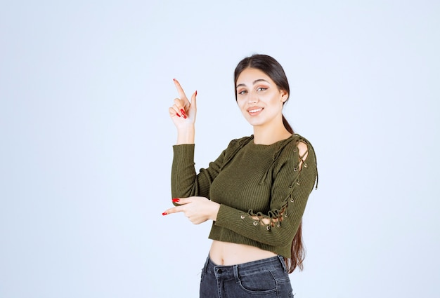Jonge lachende vrouw model omhoog met een wijsvinger.