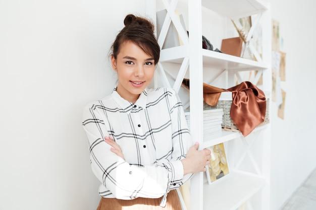 Jonge lachende vrouw modeontwerper permanent