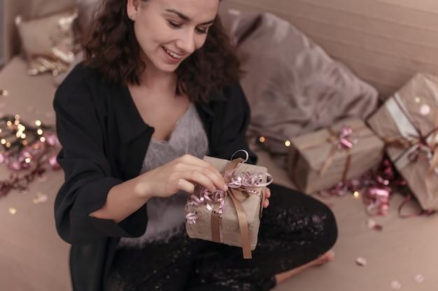 Jonge lachende vrouw pakt een kerstcadeau uit terwijl ze thuis op het bed zit.