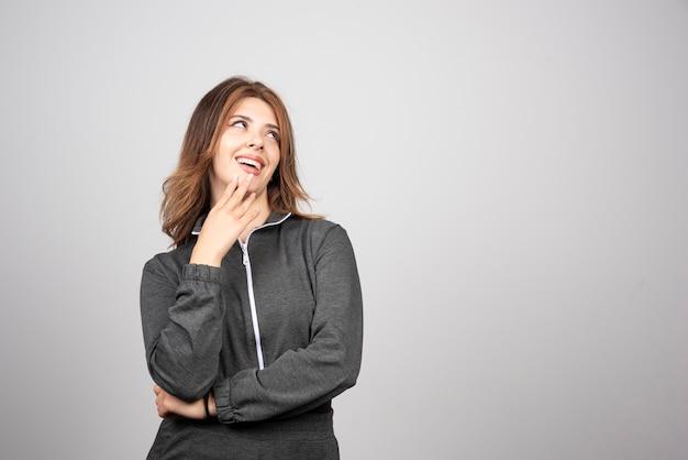 Jonge lachende vrouw permanent en poseren.