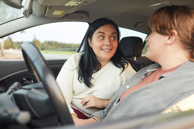 Jonge lachende vrouw praten met haar vriendin terwijl ze de auto bestuurt