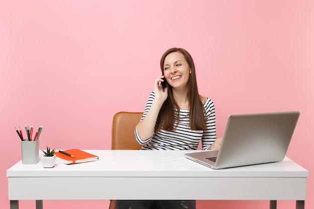 Jonge lachende vrouw praten op mobiele telefoon, aangenaam gesprek voeren zitten, werken aan project met pc-laptop geïsoleerd op pastel roze achtergrond. prestatie zakelijke carrière concept. ruimte kopiëren.