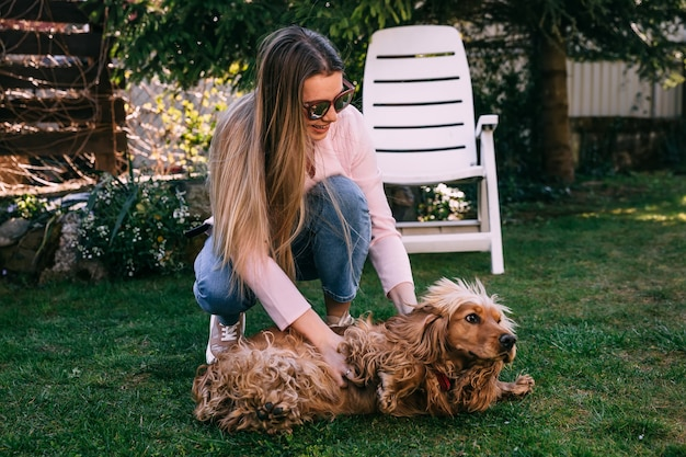 Jonge lachende vrouw speelt met haar gouden hond in de tuin.