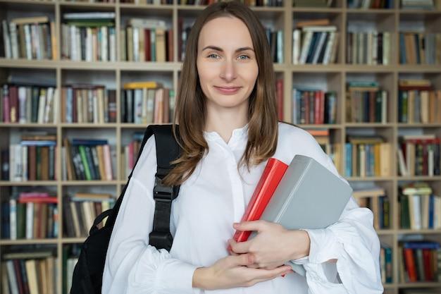 Jonge lachende vrouw staat met boeken en een rugzak in de bibliotheek
