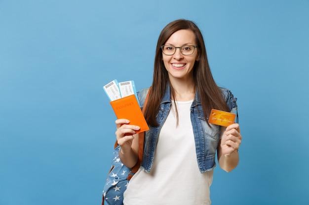 Jonge lachende vrouw student in glazen met rugzak met paspoort instapkaart tickets creditcard geïsoleerd op blauwe achtergrond. onderwijs aan hogeschool in het buitenland. vliegreis vlucht concept.