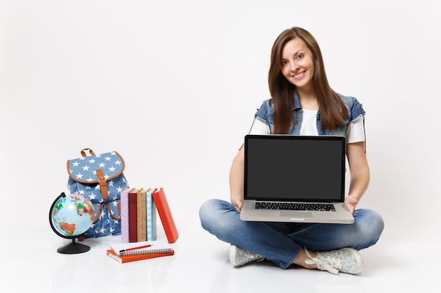 Jonge lachende vrouw student met laptop pc-computer met leeg zwart leeg scherm zitten in de buurt van globe rugzak schoolboeken geïsoleerd