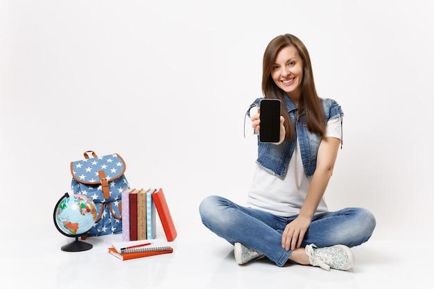Jonge lachende vrouw student met mobiele telefoon met leeg zwart leeg scherm, zittend in de buurt van globe, rugzak, schoolboeken geïsoleerd