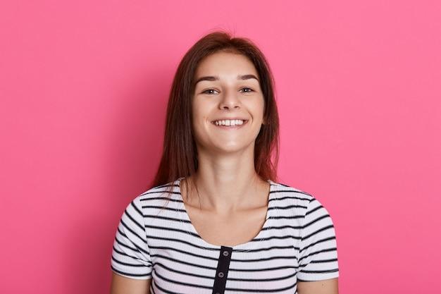 Jonge lachende vrouw tegen roze muur, poseren geïsoleerd over roze muur, gestreepte t-shirt dragen, meisje positieve emoties uitdrukken.
