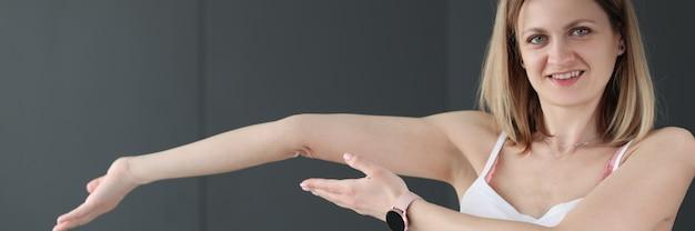 Jonge lachende vrouw toont haar gebogen arm hypermobiliteit van ellebooggewricht concept