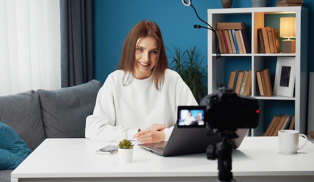 Jonge lachende vrouw video-opname op camera zittend aan tafel voor laptop in haar woonkamer
