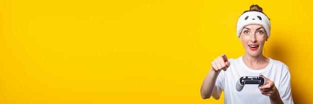 Jonge lachende vrouw wijst een vinger met een joystick in handen. banner