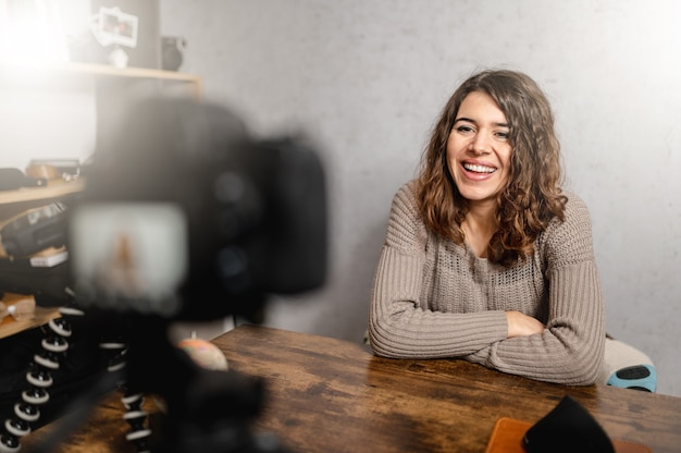 Jonge lachende vrouw zit aan het bureau te praten met de camera tijdens het nemen van een foto. vlog en freelancer concept.