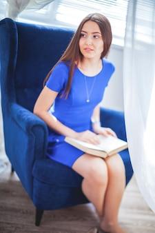 Jonge lachende vrouw zittend op een stoel.