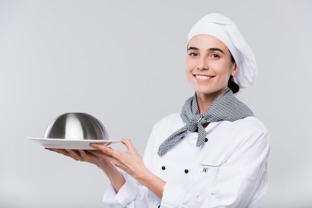 Jonge lachende vrouwelijke chef-kok in uniform op zoek naar jou terwijl je cloche met warme maaltijd voor de klant van het restaurant draagt