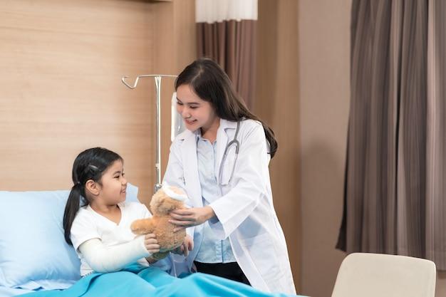 Jonge lachende vrouwelijke kinderarts arts en kind patiënt met teddybeer