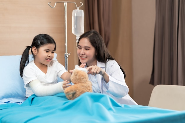 Jonge lachende vrouwelijke kinderarts arts en kind