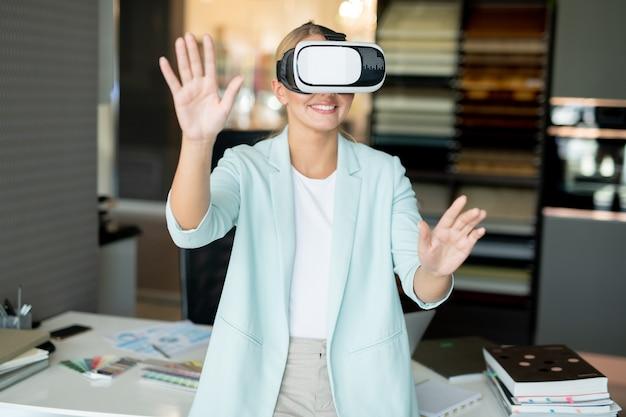 Jonge lachende vrouwelijke werknemer met vr-headset virtuele spullen tentoongesteld aan te raken tijdens het werken op kantoor