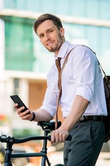 Jonge lachende zakenman gaat zitten op de fiets tijdens het gebruik van smartphone na het werk op de achtergrond van de buitenkant van het moderne gebouw