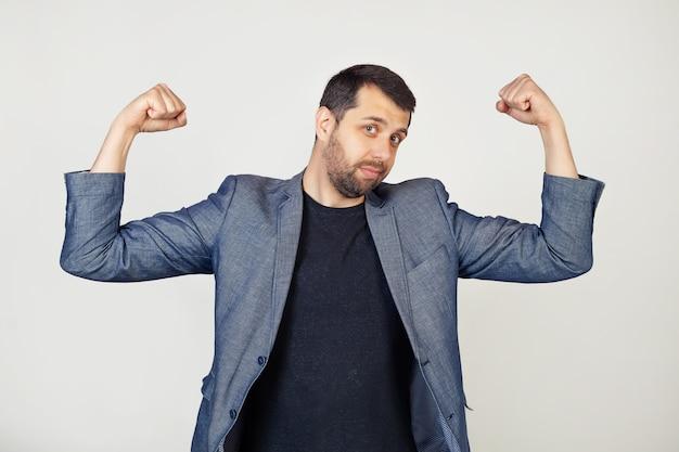 Jonge lachende zakenman man met baard in jasje met armspieren, glimlachend trots. fitness concept.