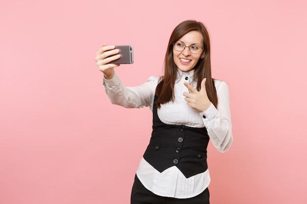 Jonge lachende zakenvrouw in glazen doen selfie schot op mobiele telefoon wijzende wijsvinger geïsoleerd op roze achtergrond. dame baas. prestatie carrière rijkdom. kopieer ruimte voor advertentie.