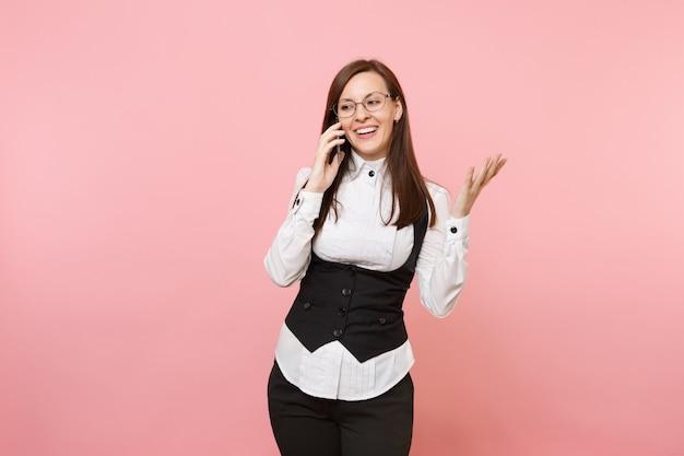 Jonge lachende zakenvrouw in glazen houden en praten op mobiele telefoon verspreiden handen geïsoleerd op pastel roze achtergrond. dame baas. prestatie carrière rijkdom. kopieer ruimte voor advertentie.