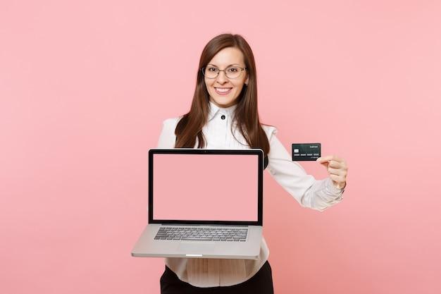 Jonge lachende zakenvrouw in glazen met creditcard, laptop pc-computer met leeg leeg scherm geïsoleerd op roze achtergrond. dame baas. prestatie carrière rijkdom. kopieer ruimte voor advertentie.