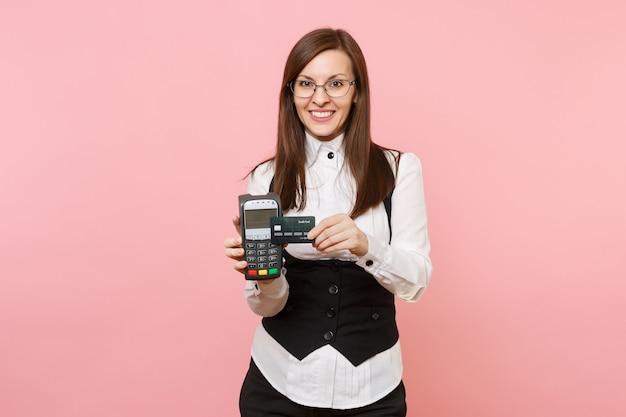 Jonge lachende zakenvrouw met draadloze moderne bankbetaalterminal om creditcardbetalingen te verwerken en te verwerven, zwarte kaart geïsoleerd op roze achtergrond. dame baas. prestatie carrière rijkdom.